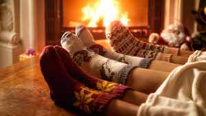 Closeup image of family feet in woolen socks lying next to fireplace